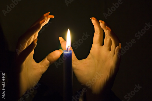 Fotografía hands over the candle's flame