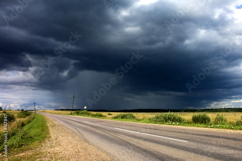 Foto auf Leinwand Onweer rain clouds near the country road.