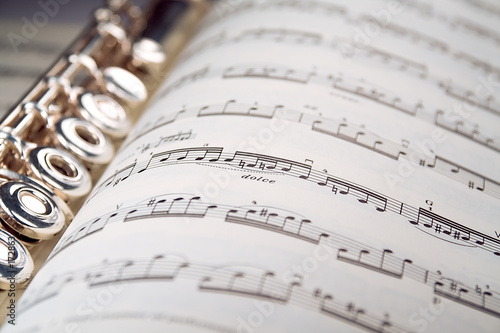 a flute rests inside a musical score