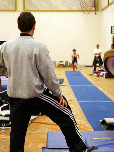 coach assisting a boy jumping on vault Canvas Print