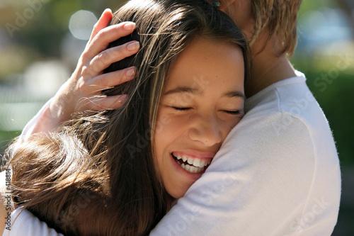 Photo mother hugging her happy daughter