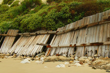 Partially Collapsed Fence On Beach