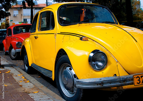 a vintage red and yellow volkswagen beetle parked