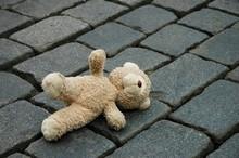 Little Teddy-bear Laying On The Cobblestones