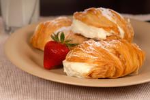 Three Sfogliatelle's With Strawberry On Tan Plate