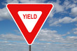 canvas print picture - yield sign with clouds