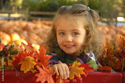 mala-dziewczynka-na-dyniowym-polu-wsrod-lisci-jesienia