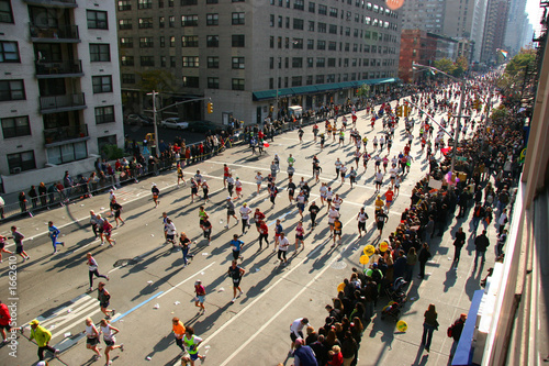 people running down the street in a marathon Fotobehang