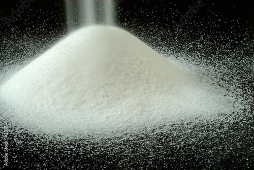 Fotografie, Obraz  sugar falls on a mountain of granulated sugar on a black backgro