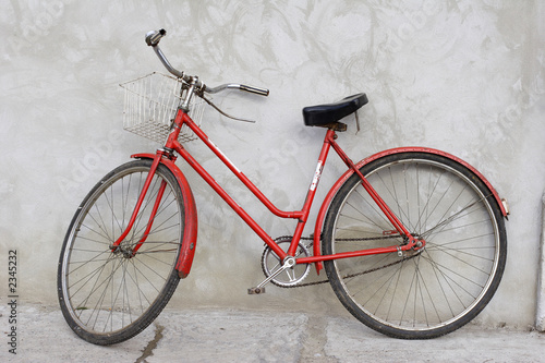 old red bicycle leaning against a wall