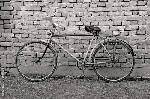 old bicycle leaning against a wall - 2345263