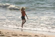 blonde girl in red playing in the ocean