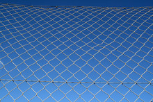 Old Metal Chain Link Security Fence And A Blue Sky