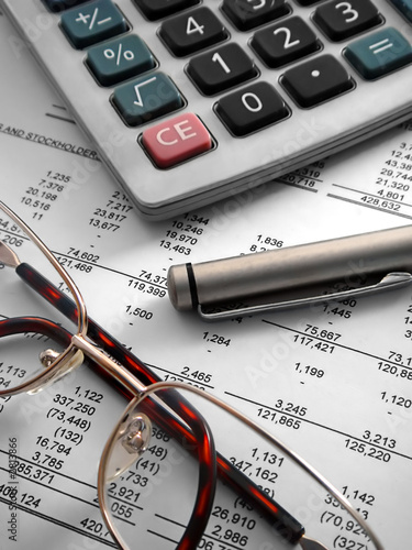 Photo calculator, pen and glasses on financial statement