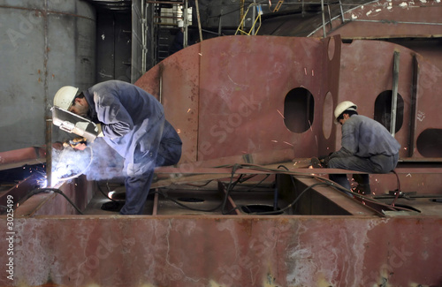 Tela Welders with protective mask welding metal at double bottom ship in a shipyard