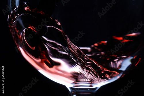 Foto op Aluminium Wijn closeup of red wine pouring