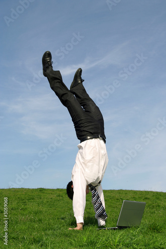 Fotografia  businessman doing handstand and using laptop outdo