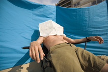 Man Covered His Face With A Paper At The Beach