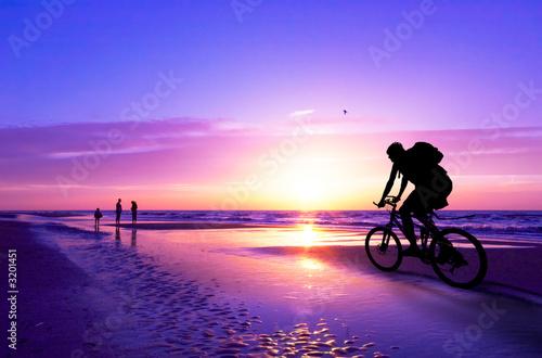 Fototapeta mountain biker on beach and sunset