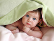Leinwanddruck Bild - beautiful baby looking out from under blanket