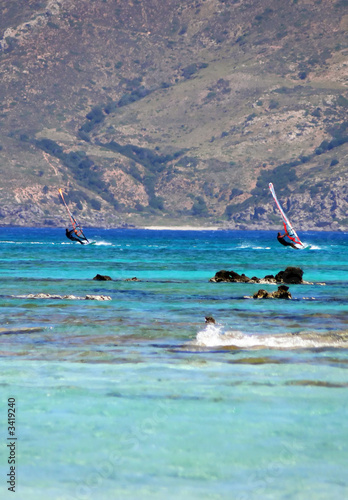 2 windsurfers in front of mountain