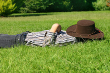 A Child Lays In Grassy Field Taking A Rest Or Siesta.
