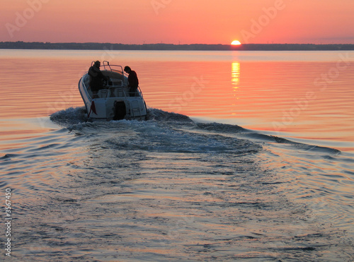 La pose en embrasure Nautique motorise Speedboat sails into the sunset