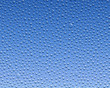 Leinwandbild Motiv Water condensation formed on glass over a blue background