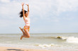 happy young woman is jumping in beach