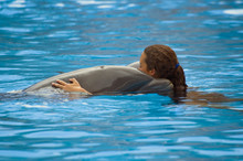 Woman Playing With Dolphin In Swimming Pool