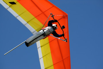 Fototapeta Yellow-red hang-glider under men control in the sky