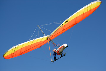 Fototapeta Orange-yellow hang-glider in the steep turn