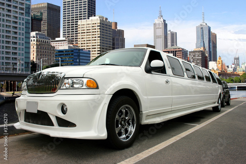 Photographie  White classy limousine waterfront and skyscrapers