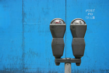 Two Parkmeters Over Blue Woode...