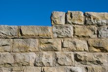 Old Sandstone Wall With Stepped Or Raised Section And Blue Sky