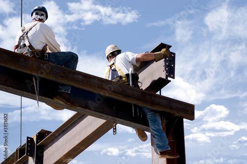 Fotografie, Obraz  Two ironworkers atop the skeleton of a modern building