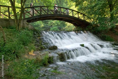 Foto op Canvas Watervallen wooden bring over small waterfall