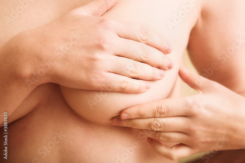 Fototapeta Woman examining her breast for signs of breast cancer