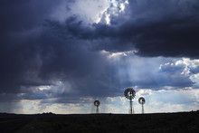 Three Wind Pumps Silhouetted A...