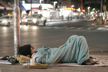 Male Homeless Sleeping In A St...