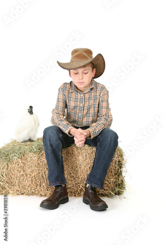 Photo Country boy sitting on lucerne bale
