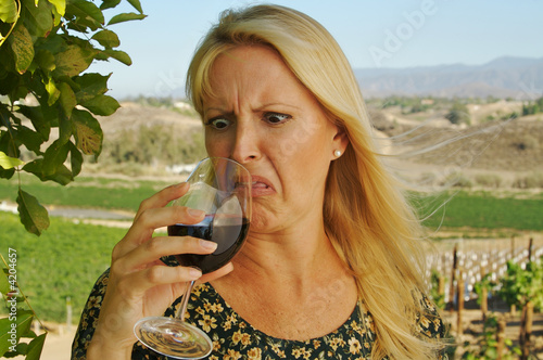 Valokuva  Beautiful woman cringes as she is wine tasting at a winery.