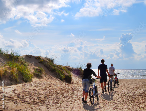 Photo Stands Cycling Three persons with bicycle go to seacoast