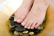 canvas print picture Pedicured feet on pebbles