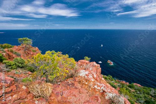 Motiv-Rollo Basic - Rochers rouge avec peu de vegetation à la bord de la mer.