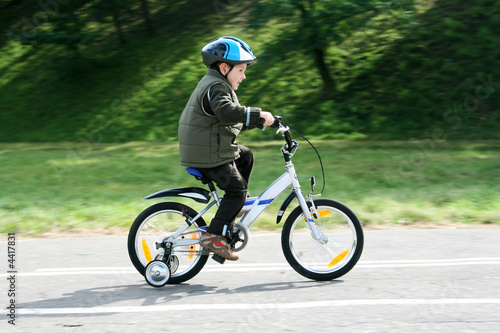 Photo Stands Cycling boy riding bike in a helmet