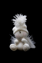 White Ceramic Gnome In Hubcap Isolated On Black