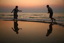 Two Seniors Running On The Beach On Sunset