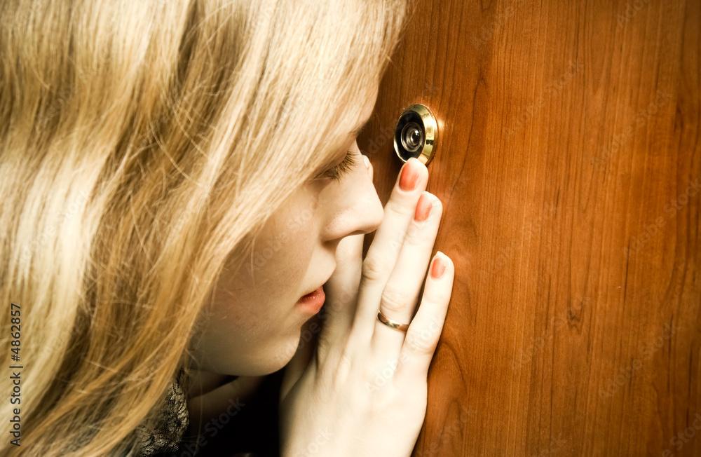 Fototapeta Woman looking into spy hole