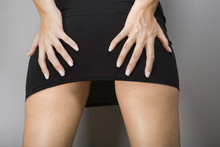Caucasian Female Wearing Miniskirt With Hands On Buttocks.